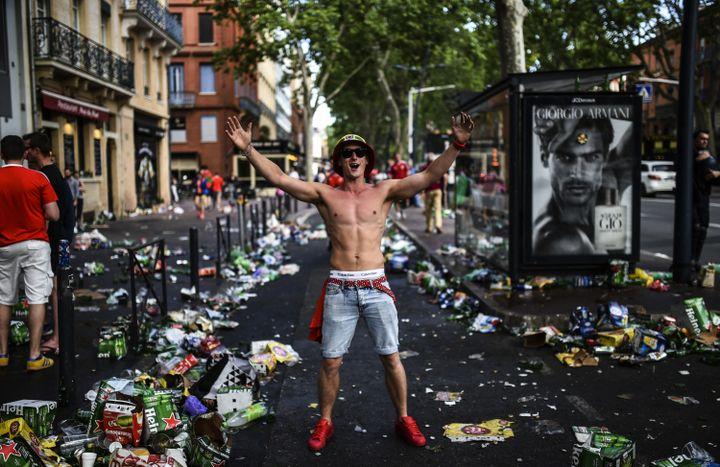 Un supporter du Pays de Galles pose fièrement au milieu d'une rue jonchée de déchets, après la victoire de son équipe face à la Russie, au Stadium de Toulouse (Haute-Garonne), le 20 juin 2016. (BULENT KILIC / AFP)