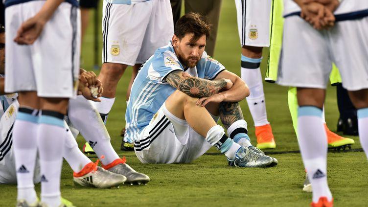 L'Argentin Lionel Messi prostré au milieu de ses coéquipiers à l'issue de la finale de la Copa America 2016 (NICHOLAS KAMM / AFP)