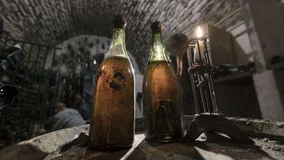Deux bouteilles de vin jaune datant de 1774, prise en photo le 22 mai 2018, dans une cave d'Arbois (Jura). (SEBASTIEN BOZON / AFP)