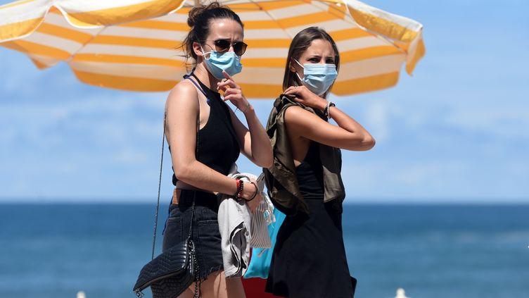 Des promeneuses portant un masque le long de la plage de Biarritz (Pyrénées-Atlantiques), le lundi 3 août 2020. (GAIZKA IROZ / AFP)