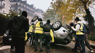 """Des casseurs renversent un véhicule lors de la troisième journée de mobilisation nationale des """"gilets jaunes"""", le 1er décembre 2018, à Paris. (SIMON GUILLEMIN / HANS LUCAS / AFP)"""