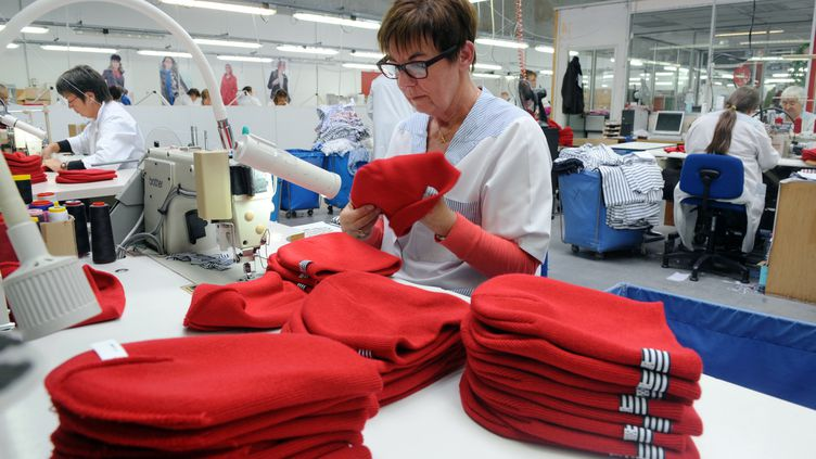 Dans l'usine d'Armor Lux, à Quimper, une employée confectionne des bonnets rouges (Finistère), le 31 octobre 2013. (FRED TANNEAU / AFP)