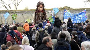La marionnette Amal haute de 3,50 m le 17 octobre 2021 dans une rue de Calais, l'une des dernières étapes de son périple de 8000 km à travers l'Europe pour sensibiliser à la cause des migrants. (FRANCOIS LO PRESTI / AFP)