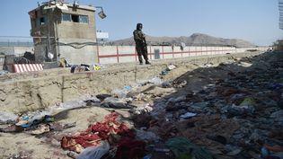 Un combattant taliban monte la garde sur le site des deux attentats suicides à Kaboul (Afghanistan), le 27 août 2021. (WAKIL KOHSAR / AFP)