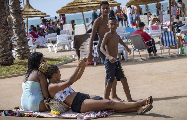 Des garçons marocains regardent des filles bronzer à la nouvelle piscine publique de la capitale Rabat, le 7 août 2019. (FADEL SENNA / AFP)