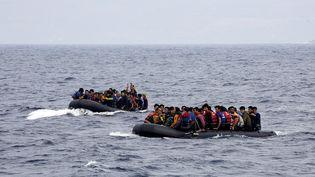 Des réfugiés à bord de deux canots pneumatiques arrivent en provenance de la Turquie sur l'île grecque de Lesbos, le 22 septembre 2015. (YANNIS BEHRAKIS / REUTERS )