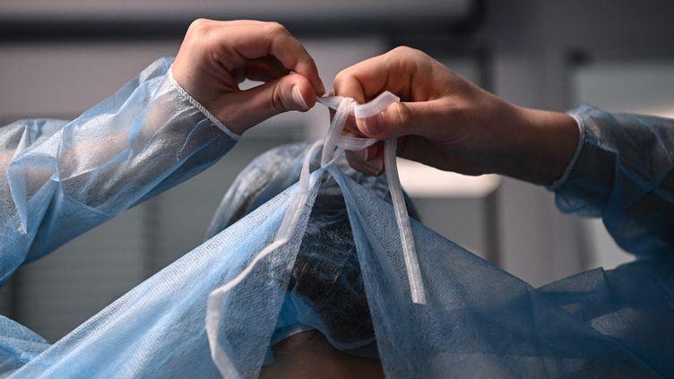 Une infirmière enfile une blouseavant d'entrer dans la chambre d'un patient infecté par le Covid-19 dans le service de réanimation de l'hôpital européen AP-HP Georges Pompidou, à Paris, le 6 avril 2021. (ANNE-CHRISTINE POUJOULAT / AFP)