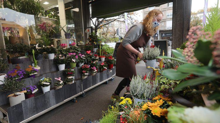 Une fleuriste prépare les arrangements de la Toussaint devant la devanture de la boutique, le 29 octobre 2020 (photo d'illustration). (VINCENT VOEGTLIN / MAXPPP)