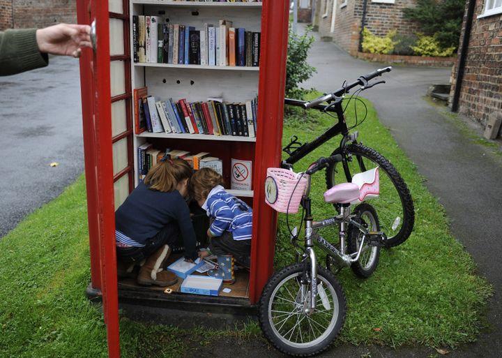 Un habitant du village de Marton cum Grafton, dans le Yorkshire du Nord (Grande-Bretagne), profite avec ses enfants d'une cabine téléphonique transformée en bibliothèque, le 9 octobre2010. (NIGEL RODDIS/REUTERS)