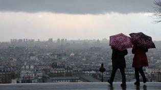 Deux personnes sous la pluie, à Paris, le 16 janvier 2018. (LUDOVIC MARIN / AFP)