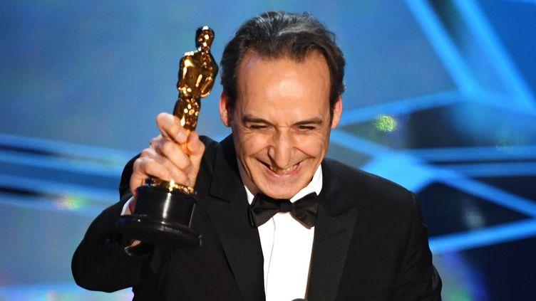 """Alexandre Desplat reçoit l'Oscar de la meilleure bande originale pour la musique de """"La forme de l'eau"""".  (Mark Ralston / AFP)"""