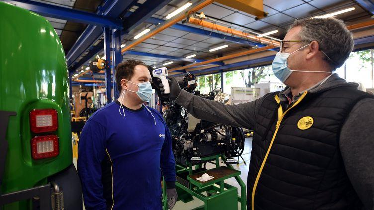 Prise de température d'un salarié sur le site de production de Mathieu-Fayat, à Toul (Meurthe-et-Moselle), le 27 avril 2020. (ALEXANDRE MARCHI / MAXPPP)
