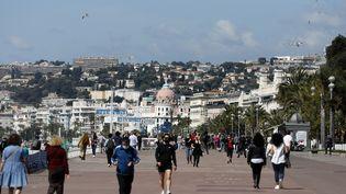 """Des personnes marchent sur la """"Promenade des Anglais"""" à Nice, le 3 mai 2021. (SEBASTIEN NOGIER / EPA / MAXPPP)"""