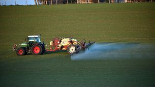 Agriculteur traitant un champ avec des pesticides près d'habitations (REMY GABALDA / AFP)