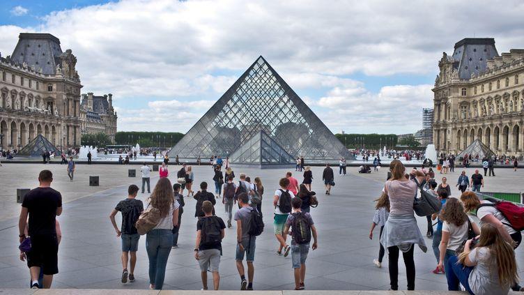 Des touristes devant la pyramide du musée du Louvre, à Paris, le 28 septembre 2016. (NICOLAS JOSE / HEMIS.FR / AFP)