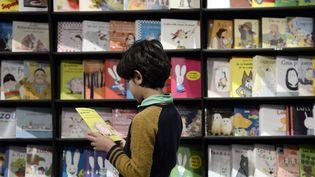 Image d'illustration. Un petit garçon choisit un livre lors du Salon du livre de Montreuil de 2014. (STEPHANE DE SAKUTIN / AFP)