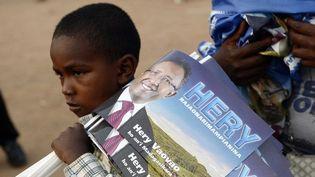 Un jeune garçon porte des drapeaux du candidat à la présidentielle, Hery Rajaonarimampianina, lors de son dernier meeting de campagne à Antananarivo, le 23 octobre 2013. (STEPHANE DE SAKUTIN / AFP)