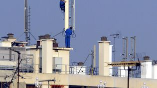 Des techniciens installent des relais téléphoniques sur le toit d'un immeuble, à Paris. (JACQUES DEMARTHON / AFP)