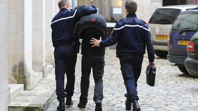 Des policiers escortent un suspect, le 21 novembre 2008, au palais de justice de La Rochelle (Charente-Maritime). (XAVIER LEOTY / AFP)