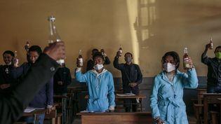 Des élèves brandissent une bouteille de Covid Organics, une tisane présentée par le président malgache Andry Rajoelina comme un puissant remède contre le Covid-19, dans le centre d'Antananarivo, le 23 avril 2020. (RIJASOLO / AFP)