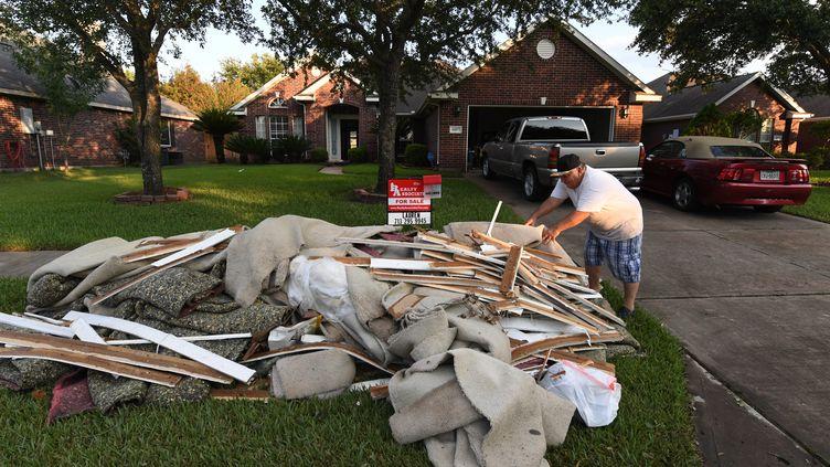 Un habitant sort les débris de sa maison après le passage de la tempête Harvey à Houston (Texas), le 31 août 2017. (MARK RALSTON / AFP)