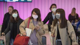 Des voyageurs portent des masques de protection à leur arrivée à l'aéroport international de Los Angeles, en Californie, mercredi 22 janvier 2020. (MARK RALSTON / AFP)