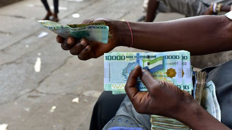 Change d'argent dans les rues de Freetown (Sierra Leone), le 30 mars 2018. (ISSOUF SANOGO / AFP)