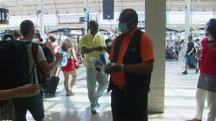 Un employé de la SNCF distribue des bouteilles d'eau à Paris, gare de Lyon, le vendredi 7 août 2020. (FRANCEINFO)