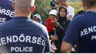 Une famille de migrants à la frontière après la fermeture par les policiers hongrois de l'accès à la voie ferrée entre la Serbie et la Hongrie à Roszke, le lundi 14 septembre 2015 (MATTHIAS SCHRADER / AP / SIPA )
