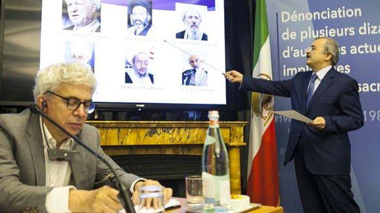 Le président de la Commission des Affaires étrangères du CNRI, Mohammad Mahadessine (debout), révélant les identités d'une soixantaine de personnes responsables des massacres en 1988, et toujours au pouvoir, en présence de William Bourdon (assis) avaocat des droits de l'homme, lors d'une conférence de presse à Paris le 6 septembre 2016. (CNRI)