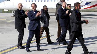 De gauche à droite, le ministre de la Défense Jean-Yves Le Drian, le président François Hollande et le ministre des Affaires étrangères Laurent Fabius, entourés des otages libérés au Niger, le 30 octobre 2013 à Villacoublay. (FRANCOIS GUILLOT / AFP)