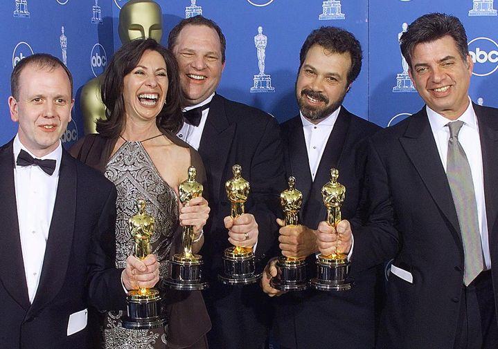 """Plusieurs membres de l'équipe de """"Shakespeare in Love""""lors de la cérémonie des Oscars, le 21 mars 1999 à Los Angeles (Etats-Unis). Harvey Weinstein est au centre, derrière la productrice Donna Gigliotti. (HECTOR MATA / AFP)"""