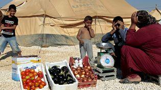 Dans le camp de Zaatari, en Jordanie, une femme vend des légumes, le 3 janvier 2013. (KHALIL MAZRAAWI / AFP)