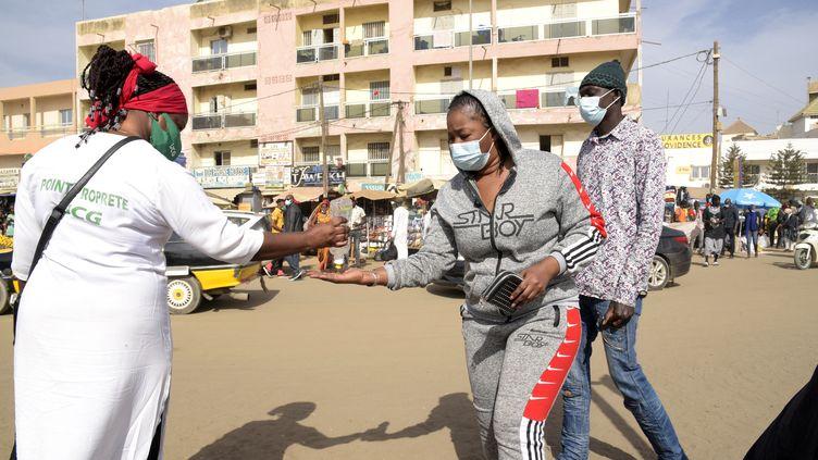 Une bénévole distribue du gel hydroalcoolique aux passants dans les rues de Dakar (Sénégal), le 22 janvier 2021. (SEYLLOU / AFP)
