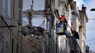 Des pompiers font face aux décombres de deux immeubles effondrés, rue d'Aubagne à Marseille, le 8 novembre 2018. (GERARD JULIEN / AFP)