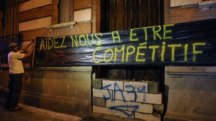 Un membre des Jeunes Agriculteurs installe une bannière sur le siège des Républicains, jeudi 20 août 2015 à Toulouse (Haute-Garonne). (REMI GABALDA / AFP)