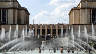 Des personnes tentent de se rafraîchir à la fontaine du Trocadéro, le 25 juillet 2018 à Paris. (BERTRAND GUAY / AFP)