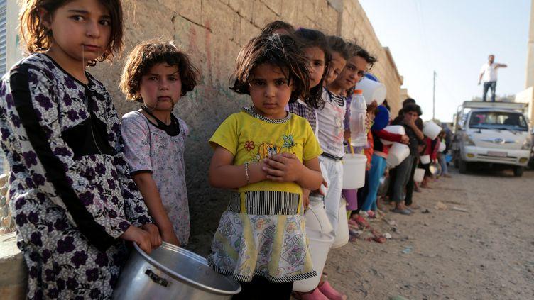 Des enfants syriens attendent recevoir un repas dans la ville de Raqqa (Syrie), le 14 juillet 2013 (MEZAR MATAR / AFP)
