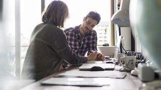 Une femme aide un homme à remplir un dossier. Photo d'illustration. (FR?D?RIC CIROU / MAXPPP)