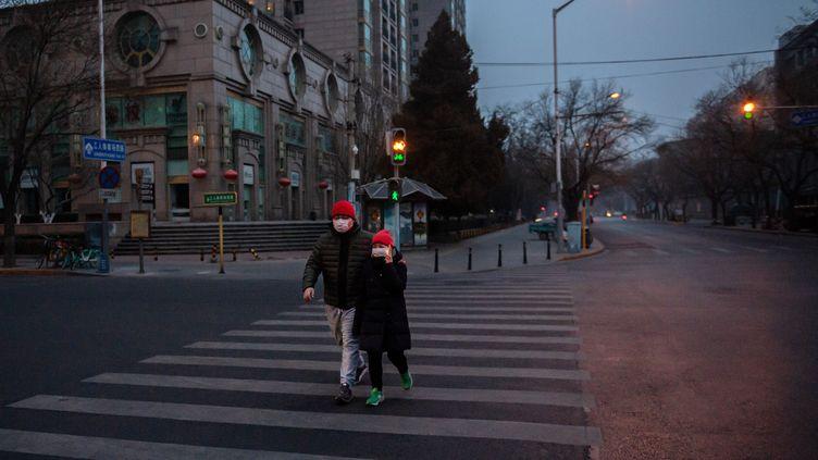 Un couplemarche dans une rue de Pékin le 28 janvier 2020. (NICOLAS ASFOURI / AFP)