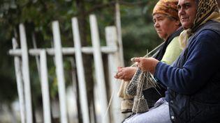 Deux retraitées tricotent sur un banc à Viscri, un village de Transylvanie, en Roumanie. (KARINA KNAPEK / AFP)