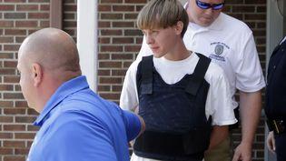 Dylan Roof, l'auteur présumé de la fusillade qui a fait neuf morts dans une église noire de Charleston (Caroline du Sud, Etats-Unis), est escorté hors du commissariat de Shelby (Caroline du Nord), le 18 juin 2015. (CHUCK BURTON / AP / SIPA)