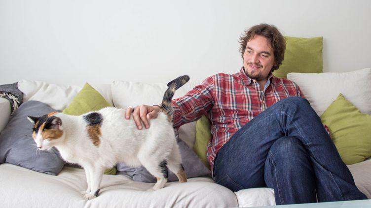 Militant écologiste devenu défenseur du véganisme, Olivier pose avec l'un de ses chats à son domicile d'Asnières (Hauts-de-Seine), le 18 mars 2014. (MATHIEU DEHLINGER / FRANCETV INFO)