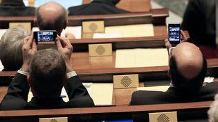 Des députés immortalisent la dernière séance de la législature avec leur téléphone portable, le 6 mars au Palais Bourbon. (JACQUES DEMARTHON / AFP)