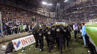 Des CRS sécurisent le terrain du stade Vélodrome lors du match OM-Lyon, marqué par des jets de projectiles, dimanche 20 septembre 2015. (FRANCK PENNANT / AFP)