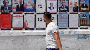Un homme passe devant des affiches électorales collées le long d'un mur, le 7 septembre 2019 à Tunis. (FETHI BELAID / AFP)