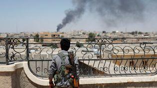 Un combattant kurde regarde de la fumée s'échapper après une frappe de la coalition contre Raqqa (Syrie), le 16 juin 2017. (GORAN TOMASEVIC / REUTERS)