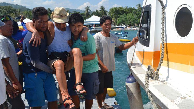 Des secouristes indonésiens viennent en aide à un passager blessé du Ferry, àSengigi (île de Lombok en Indonésie), le 6 juin 2015 (FAIZ ABDILLAH / AFP)