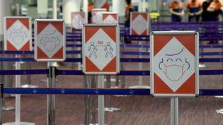 Des panneaux informatifs le long d'une file d'attente dans le terminal 2E de l'aéroport Roissy-Charles de Gaulle, le 18 mars 2021. (ERIC PIERMONT / AFP)