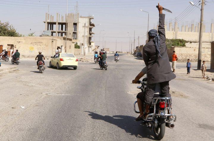 Des hommes paradent pour célébrer la prise de la ville deTabqa,située près de Raqqa (Syrie), par l'organisation Etat islamique, le 24 août 2014. (REUTERS)